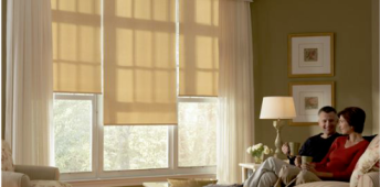 Man and woman in living room golden roller shades with drapery panels